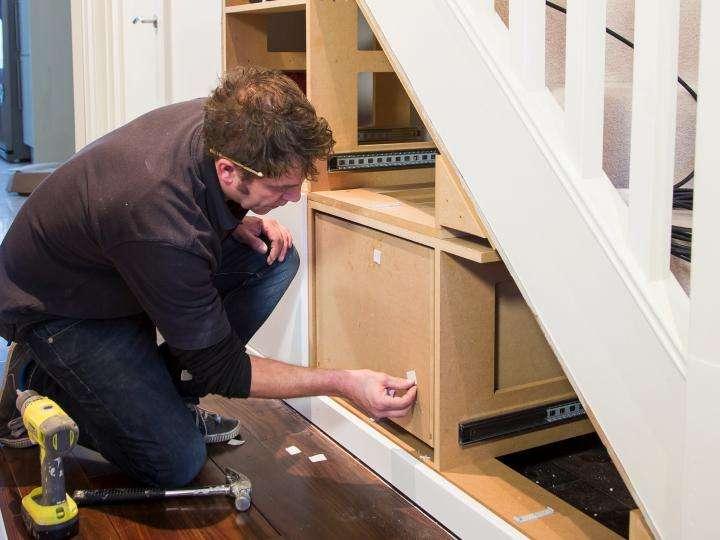 Tradesman Installing an Under Stairs Storage Unit